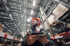 Pakhuismanager die zijn inventaris in een groot pakhuis controleren royalty-vrije stock foto's