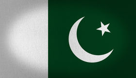 Pakistan flag. Composed by two vertical lines, green and white graphic, burn green at the right side with a crescent moon and a star, fabric texture background Stock Photo