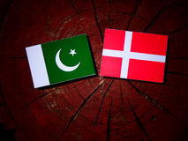 Pakistan flag with Danish flag on a tree stump isolated. Pakistan flag with Danish flag on a tree stump Royalty Free Stock Photography