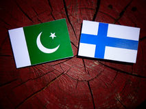 Pakistan flag with Finnish flag on a tree stump isolated. Pakistan flag with Finnish flag on a tree stump Royalty Free Stock Photos