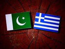 Pakistan flag with Greek flag on a tree stump isolated Stock Photos