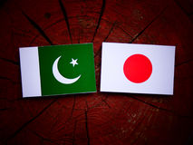 Pakistan flag with Japanese flag on a tree stump isolated Stock Photography