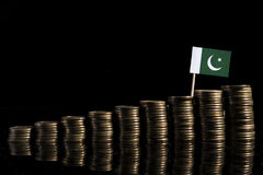 Pakistan flag with lot of coins  on black Royalty Free Stock Photography