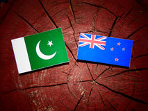 Pakistan flag with New Zealand flag on a tree stump isolated. Pakistan flag with New Zealand flag on a tree stump Royalty Free Stock Images