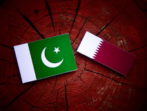 Pakistan flag with Qatari flag on a tree stump isolated Royalty Free Stock Photography
