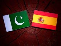 Pakistan flag with Spanish flag on a tree stump  Stock Photos