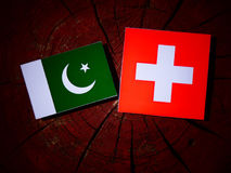 Pakistan flag with Swiss flag on a tree stump  Royalty Free Stock Photos