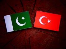 Pakistan flag with Turkish flag on a tree stump  Royalty Free Stock Photos