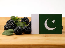Pakistan flag on a wooden panel with blackberries isolated on a. White background Royalty Free Stock Photos