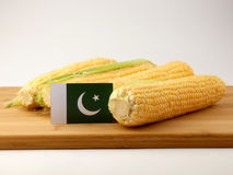 Pakistan flag on a wooden panel with corn isolated on a white ba. Ckground Stock Photo