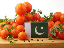 Pakistan flag on a wooden panel with tomatoes isolated on a whit. E background Stock Photo