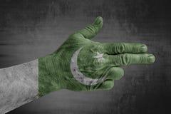 Pakistan-Flagge gemalt auf männlicher Hand wie einem Gewehr stockbild