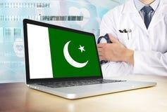Pakistan-Gesundheitssystem im Technologiethema Pakistanische Flagge auf Bildschirm Doktor, der mit Stethoskop im Krankenhaus steh stockbild