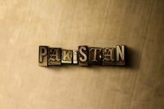 PAKISTAN - närbild av det typsatta ordet för grungy tappning på metallbakgrunden Arkivfoton