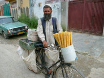 Pakistani Bicycle Ice Cream Cone Seller. A Pakistani man sells ice cream cones from his bicycle in the hill town of Mansehra in northern Pakistan Stock Photos