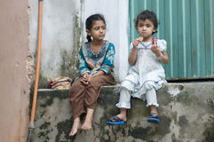 Pakistani children eating having party time. Two little girls at a local street in Pakistan doing chit chat and having party royalty free stock photography