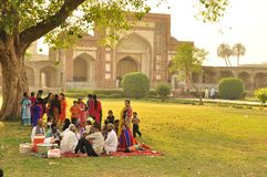 Pakistani family having a large picnic. Under a tree inside  the garden surrounding the Tomb of emperor Jahangir, Pakistan, Lahore Royalty Free Stock Photo