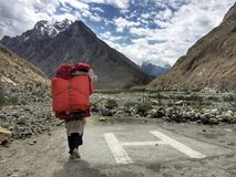 Pakistani male porter walk pass helicopter landing pad in mountain area. Pakistani male porter carries heavy camping equipment and walks pass helicopter landing Stock Photo