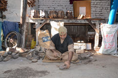 Pakistani Man Making Shoes. A Pakistani man making hand-made shoes in Lahore`s famous food street Royalty Free Stock Photography