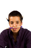 Pakistani schoolboy is playing funny with pencils Royalty Free Stock Image
