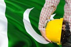 Pakistanischer Ingenieur hält gelben Schutzhelm mit dem Wellenartig bewegen des Pakistan-Flaggenhintergrundes Bau- und Geb?udekon stockfotos