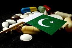 Pakistansk flagga med lotten av medicinska preventivpillerar som isoleras på svart backg Fotografering för Bildbyråer