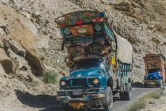 Pakistanska dekorerade lastbilar transporterar gods via den Karakoram huvudv?gen, Pakistan royaltyfri fotografi