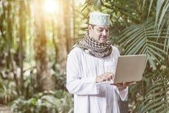 Pakistanska muslim Man anseende och arbete på anteckningsboken royaltyfria foton