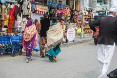 Pakistanskt folk i traditionell klänning som går på shoppinggatan arkivfoton