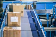 Pakketten op transportbanden met vage industriële achtergrond Royalty-vrije Stock Foto's