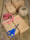 Pakketten in pakpapier en koord met lint en scisso worden verpakt die Royalty-vrije Stock Afbeeldingen