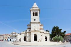 Pakostane, Croatia - AUGUST 27, 2017 - Tourists walking around the church steeple of Pakostane stock images