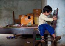 PAKSE, LAOS, el 14 de agosto: Una sentada no identificada del niño pequeño de Laos Foto de archivo libre de regalías