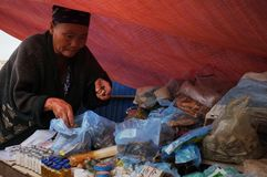 local elderly woman selling traditional tribal medicines and remedies at the market