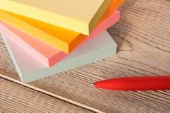 Pakunki kolorowi majchery dla notatek i pióro na drewnianym stole obrazy royalty free