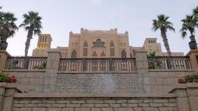 Palácio árabe com a cerca de pedra autêntica no crepúsculo com jardim e canteiros de flores da palma filme