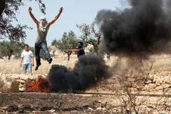Palästinensischer Mann, der über Feuer am Protest springt Stockbild