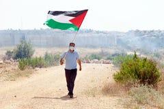 Palästinensischer Protestierender, der Flagge durch Wand des Trennungs-Westbas hält Stockfotos