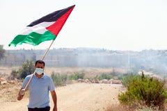 Palästinensischer Protestierender, der Flagge durch Wand des Trennungs-Westbas hält Lizenzfreie Stockbilder