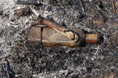 Paląca szklana butelka kłama w popiółach wygasły ogień obrazy stock