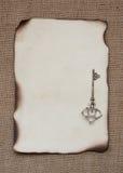 Palący papier z srebro kluczem obraz stock