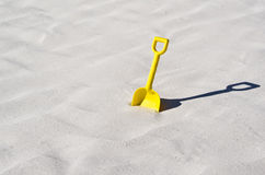 Pala amarilla del juguete en una playa blanca hermosa de la arena Foto de archivo