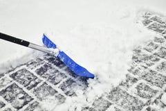 Pala azul borrosa de la nieve en nieve profunda Imagen de archivo libre de regalías