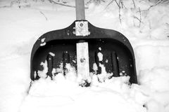 Pala de la nieve en la nieve blanca imagenes de archivo