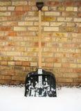 Pala de la nieve en la nieve en un fondo de una pared de ladrillo imágenes de archivo libres de regalías