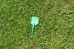 Pala verde dei bambini che risiede nell'erba immagini stock