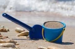 Pala y compartimiento en la arena Foto de archivo
