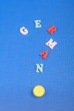 Palabra alemana en el fondo azul compuesto de letras de madera del ABC del bloque colorido del alfabeto, espacio de la copia para Fotografía de archivo libre de regalías