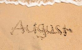 Palabra augusta en la playa arenosa Imagen de archivo libre de regalías