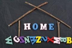 Palabra CASERA en el fondo negro compuesto de letras de madera del ABC del bloque colorido del alfabeto, espacio del tablero de l Fotos de archivo